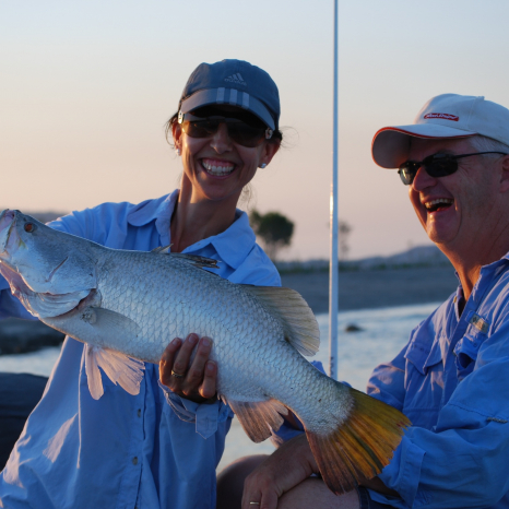 couple with caught barramundi sunset